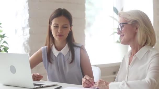 Starší klient mladý výkonný ředitel po dosažení dohody potřásaje si rukama