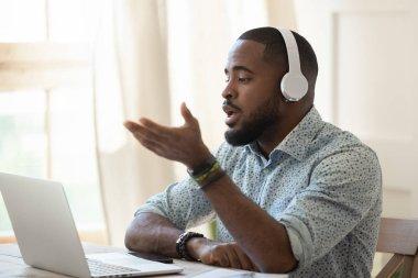 African male skype teacher wearing headphones talking looking at laptop