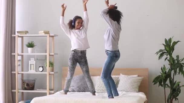 Vegyes verseny anya és lánya élvezze a zenét táncol ágyon
