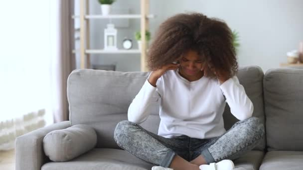 African pre-teen girl sitting on couch crying feels unhappy
