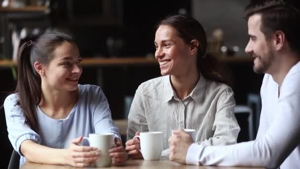 Diverse friends drinks tea talking spending time in cafe