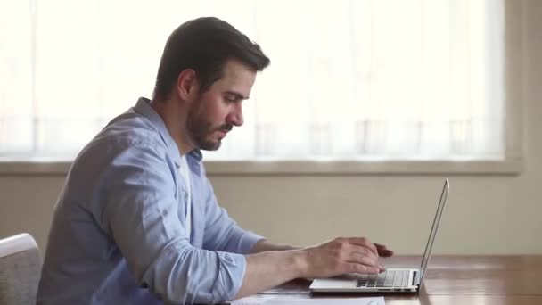 Young focused man sitting at desk working on computer