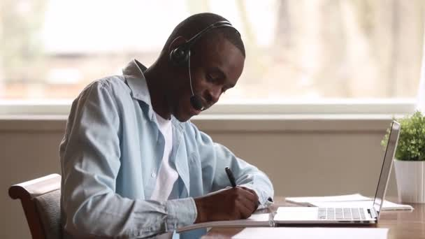 African guy wearing headset learns foreign languages online using laptop