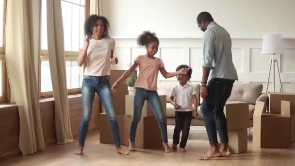 African couple with kids dancing near big boxes celebrating relocation