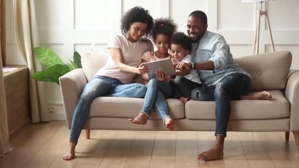 Africká rodina s dětmi používající tabletový počítač se zábavou uvnitř