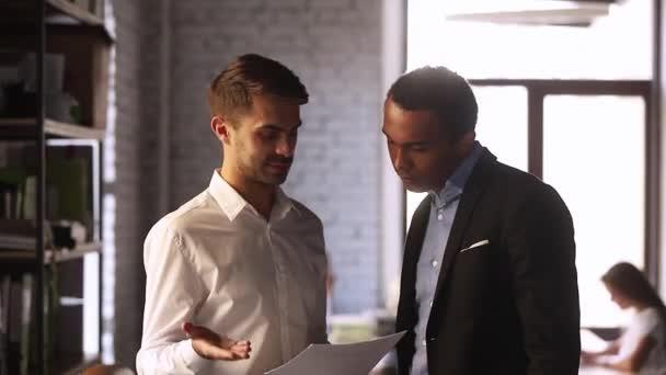 Různorodé podnikatelé diskutují o dokumentu podrobnosti dokončení schůzka třesoucí se ruce