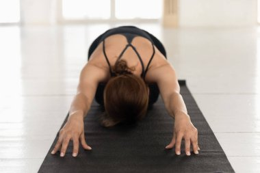Young woman practicing yoga, relaxing in Child pose, Balasana exercise