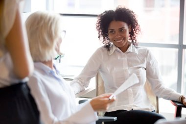 Smiling diverse colleagues talk discussing paperwork at workplace