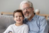 glücklicher alter Opa umarmt kleinen Enkelsohn und blickt in die Kamera