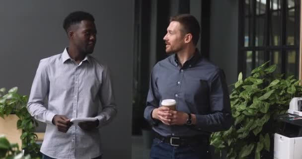 Two happy diverse male partners talking handshaking standing in office
