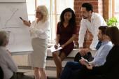 Fotografie Geschäftsfrau mittleren Alters macht Whiteboard-Präsentation für Kollegen