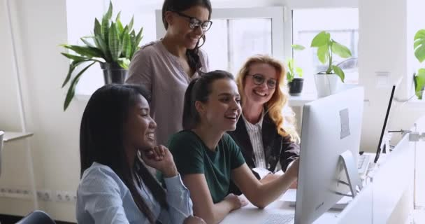 Happy multiethnic young and older businesswomen working together on computer