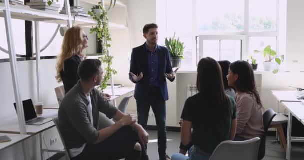 Selbstbewusste männliche Führungskraft spricht mit vielseitigem freundlichem Team im Amt