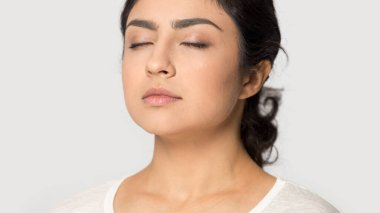 Close up side view of beautiful millennial indian girl isolated on grey studio background meditating with eyes closed, peaceful calm young ethnic woman relive negative emotions, breathe fresh air stock vector