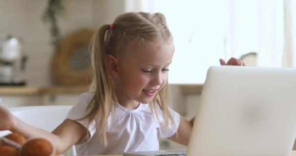 Kíváncsi aranyos kislány használja laptop egyedül otthon