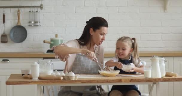 Šťastná maminka a malé dítě dcera bití těsto v kuchyni
