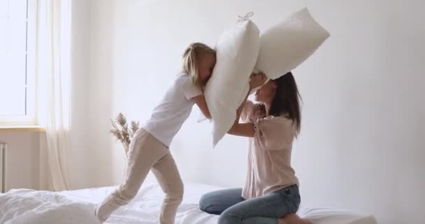 Happy family mom and daughter enjoy pillow fight on bed