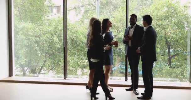 Multiethnic male and female professional colleagues talk stand in office