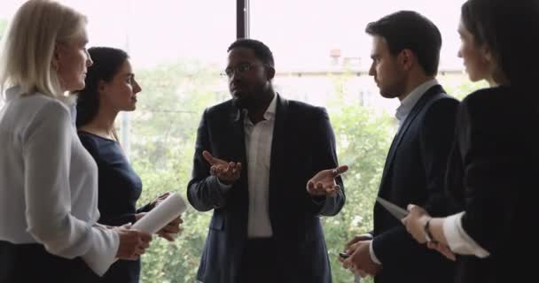 African businessman coach communicating with business people standing in office