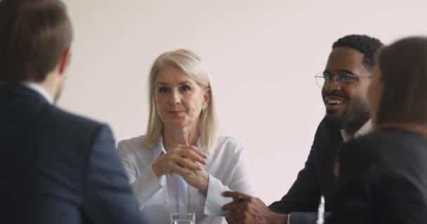 Šťastná starší žena korporátní vůdce mluvit s partnery u stolu