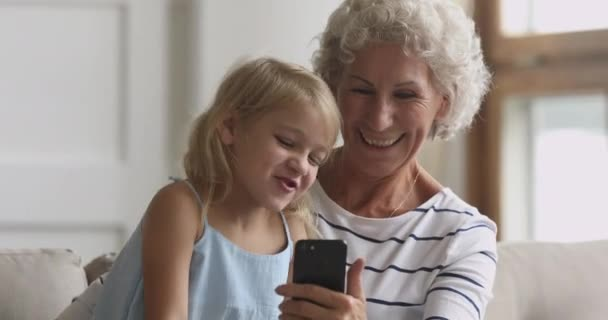 Happy senior grandmother and grandchild using smart phone at home