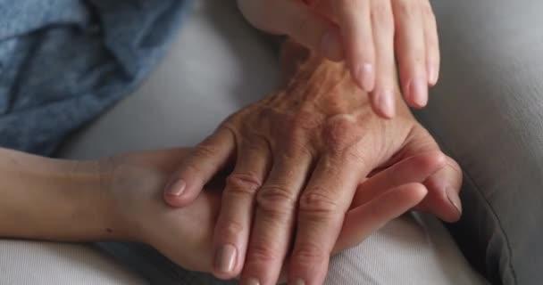 Mladá žena držení staré babičky ruce zblízka pohled