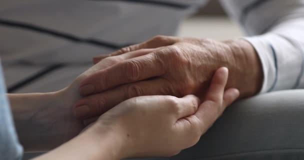 Nahaufnahme von jungen weiblichen Händen, die alte Omas Arm halten