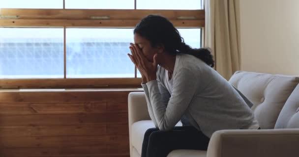 Depressziós afrikai nő érzés ideges ülni kanapén otthon