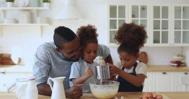 Roztomilý africký rodinný otec a malí sourozenci připravují těsto společně