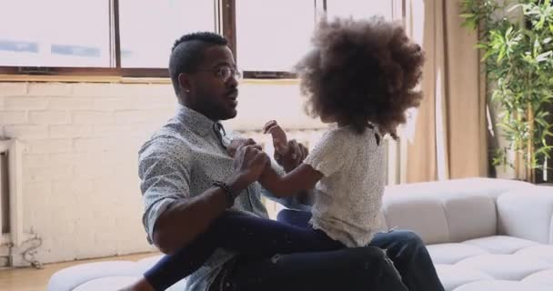 African father laugh play with cute child daughter on sofa
