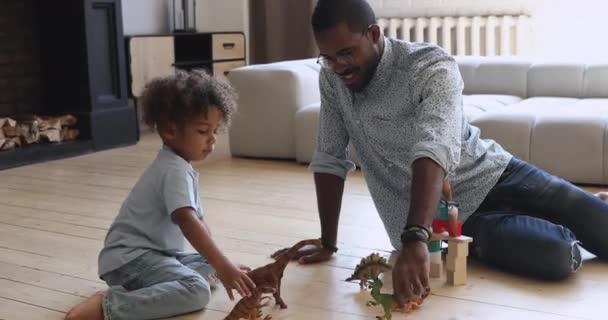 Happy american dad and small son playing dinosaurs at home