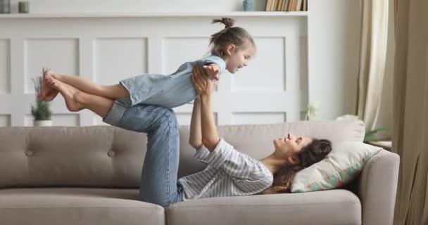 Šťastná maminka zvedání roztomilé dítě dcera hrát letadlo na pohovce