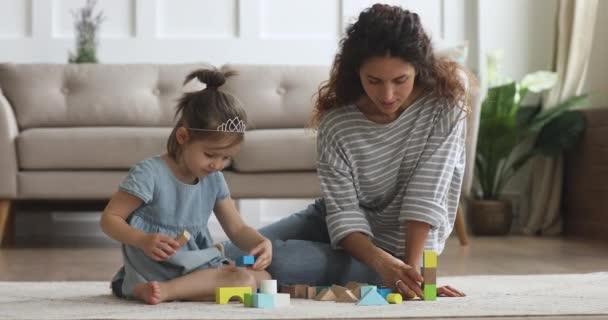Šťastná maminka pomáhá dítě dcera budova hrad dřevěných bloků
