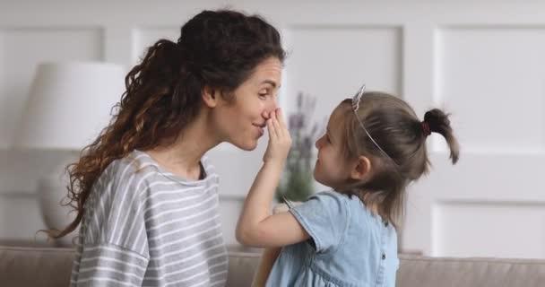 Šťastná maminka a malé dítě dcera dotýkat nosy smích bonding