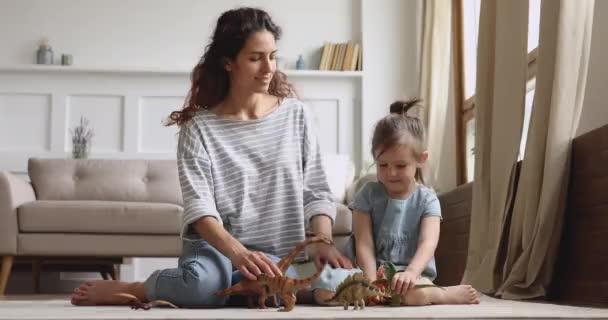 glückliche Mutter mit kleiner Tochter spielen Dinosaurier sitzen auf dem Boden