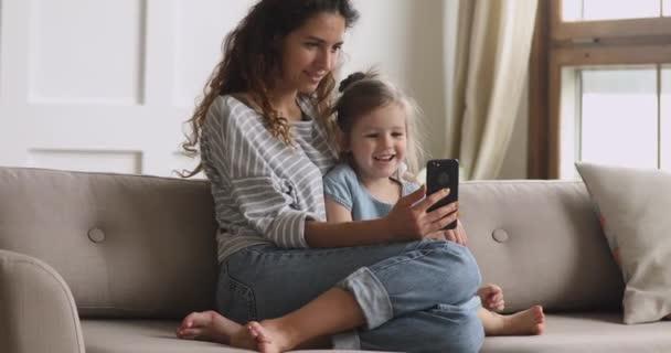 Glückliche Mutter und kleine Tochter lachen beim Anblick des Telefons