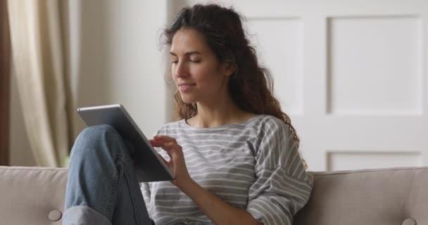 Šťastná mladá žena relaxuje doma na pohovce pomocí tabletu