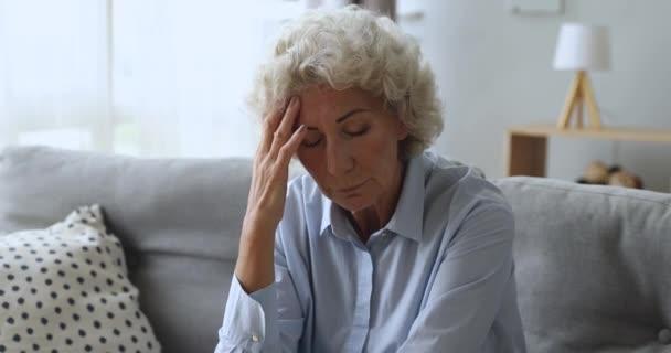 Depressziós aggódó idős nő fejfájás vagy mentális stressz koncepció