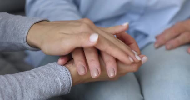 Young woman daughter caregiver holding hand helping old grandma, closeup