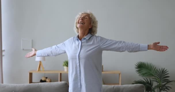 Overjoyed senior woman standing in living room with arms outstretched