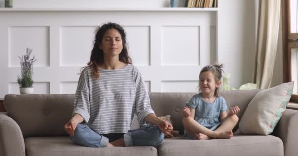 Funny cute kid daughter meditating laughing with mom at home
