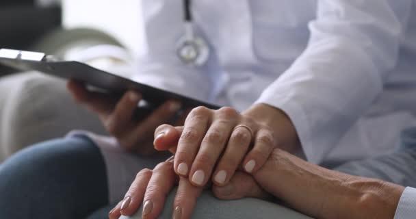 Női orvos fogja a kezét idősebb nagymama beteg, közelkép