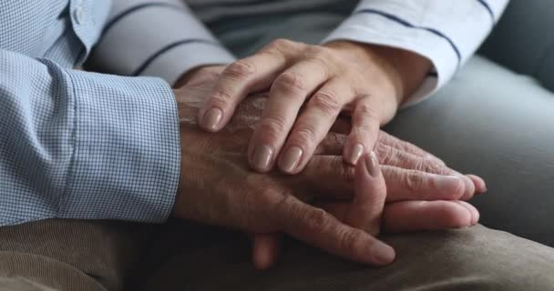 Caring elderly wife holding hand of senior grandpa give empathy