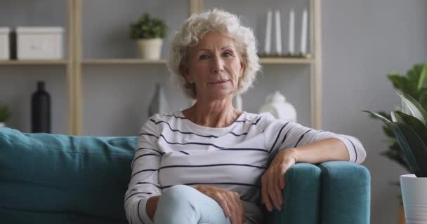Boldog idős nő néz kamera ül a kanapén