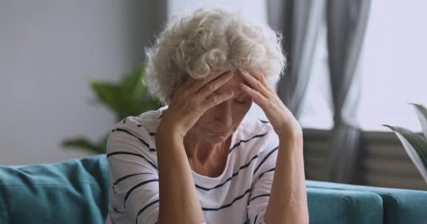 Aggódó idős hölgy ül egyedül érzés fejfájás mentális stressz