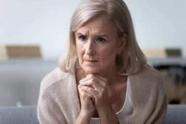 Worried mature woman feel concerned about health problems at home
