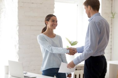 Confident middle aged male boss shaking hands with happy young mixed race female intern employee, holding envelope with money reward, congratulating with good work results, encouraging coworker. stock vector