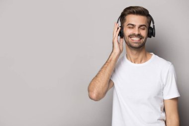 Smiling caucasian man listen to music in Bluetooth modern headphones