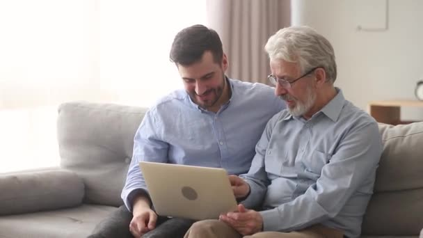 Elderly father and son sitting on couch laughing watching video