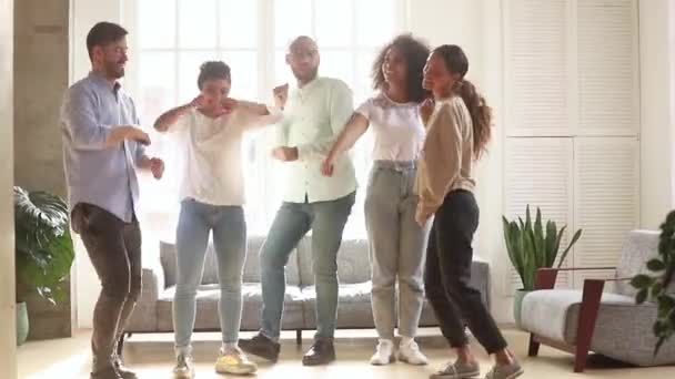 Multi racial friends dancing in living room enjoy time together